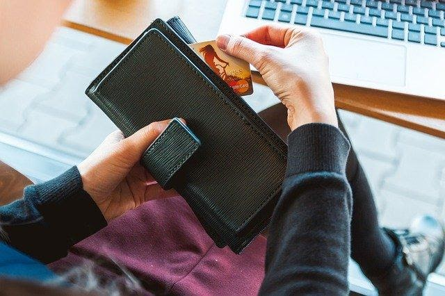 close up view of woman pulling credit card out of wallet