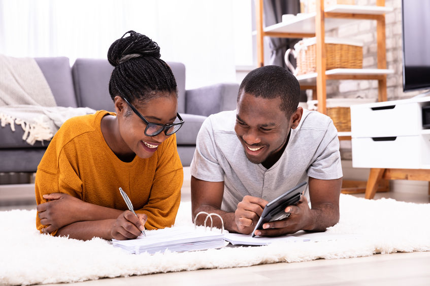 African Couple Calculating Invoice With Calculator