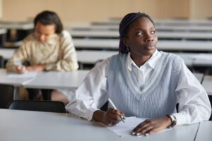 two female college students sit in a classroom taking notes
